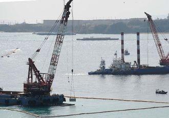 台船がクレーンで、大浦湾にブロックを沈める作業を続けた=29日午後0時49分、名護市辺野古沖