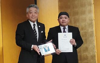 表彰状と記念の盾を受け取る御菓子御殿の澤岻英樹社長(右)=17日、東京・新宿の京王プラザホテル