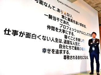 社内に掲げる「行動規範」をアピールする琉球インタラクティブの臼井隆秀社長=宜野湾市大山