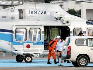 海上保安庁のヘリから八重山病院へ行く車両に乗り移る中国漁船の乗員ら=8月11日午後6時44分、石垣市真栄里