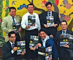 仲間一町長(後列中央)にガイドブックの完成を報告した関係者ら=16日、金武町役場