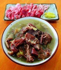 糸満市真栄平にある玉城やぎ料理店のヤギ汁(手前)とヤギの刺し身