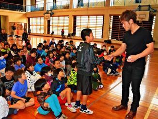 マジックの手伝い役の男子児童と握手を交わすMASAさん(右)=国頭村奥間、奥間小学校