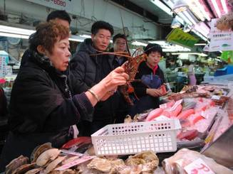 A clerk holds up an Ise-ebi (Japanese spiny lobster) at a market in Naha, Okinawa Prefecture.   THE OKINAWA TIMES