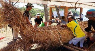 本番に向け、島に自生するヒメガマで草舟製作に当たるプロジェクト関係者ら=5日、与那国町久部良・ナーマ浜(金井瑠都通信員撮影)
