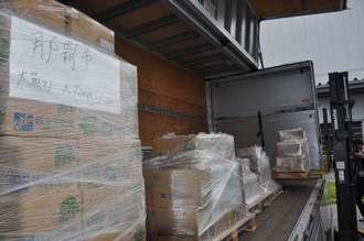 トラックに次々と積み込まれる投票用紙=7日午前、糸満市内