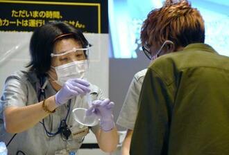 到着客(手前)に検査のための唾液採取方法を説明する検疫所の担当者=8月3日、成田空港
