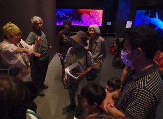 作者の本間ますみさんの話に聞き入る来場者ら=3日、那覇市の県立博物館・美術館