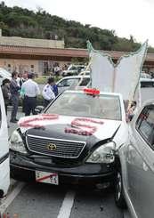 駐車車両2台に衝突した改造車両(中央)=8日午後2時10分ごろ、南風原町立中央公民館