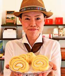 ジーマーミ豆腐入りのロールケーキを持つ店長の高嶺美緒さん=9日、那覇市