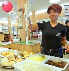 「パンもいいけど、そばも食べてね!」と麺を持ち上げ勧めるパン屋の店員。今や沖縄そばはカンポグランデの市民食だ=カンポグランデ市内