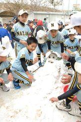 冷たい雪の感触を楽しみ、雪だるまを作って遊ぶ少年野球チームの子どもたち=1日、名護市民球場