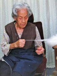 真綿から横糸を紡ぐ山城ハツさん=久米島町真謝の自宅(提供)