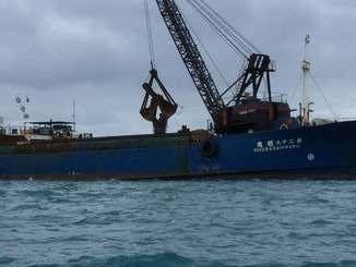 護岸に接岸した台船に土砂を積む作業が進んでいる=12日、名護市辺野古