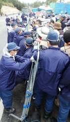 「市民を不当に拘束する違法な柵だ」として、柵をはさんで機動隊ともみ合う市民(右手奥)=17日、名護市辺野古