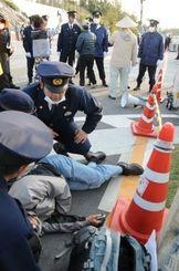 県警機動隊ともみ合いになり、息苦しさを訴える男性。機動隊員によってゲート脇に移動された=25日午前7時10分ごろ、名護市辺野古