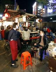 中洲の屋台に設置されたテラス席で食事をする男性客(手前右)=30日夜、福岡市博多区