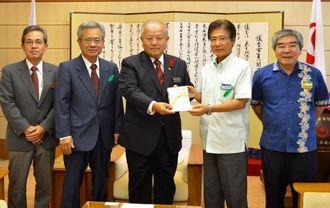喜納会長に目録を手渡す沖縄海邦銀行の金城常務(右から2人目)=7日、県議会議長室