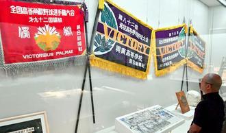 甲子園春夏の優勝旗(レプリカ)など高校野球の貴重な資料が並ぶ=2日、那覇市の県立博物館・美術館