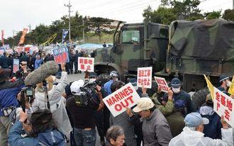 市民らが「米兵の犯罪許さないぞ」という声を上げる中、基地内に入る米軍車両=16日、名護市辺野古の米軍キャンプ・シュワブゲート前