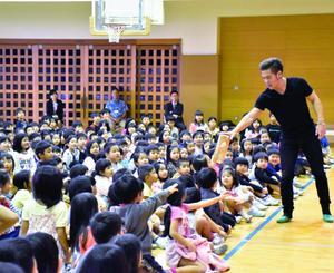 MASAさん(右)のマジックに興味津々で見入る子どもたち=13日、浦添市・当山小学校