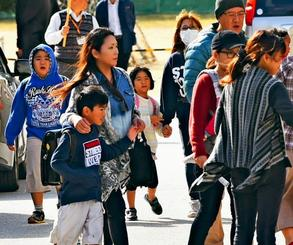 不安げな表情で児童を迎え、手をつないだり肩を抱いたりしながら学校を後にする父母ら=日午後1時50分、宜野湾市・普天間第二小学校(金城健太撮影)