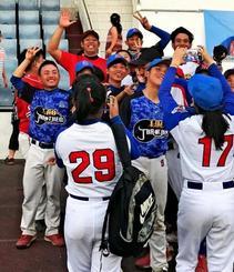 ラオス国際野球大会で地元の野球チームと写真撮影する糸数さんら=1月、ラオス・ビエンチャン(金さん提供)