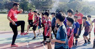 台湾の子どもたちに足の上げ方を伝えるアスリート工房の譜久里武代表(左)=2020年1月、台湾(スポーツデータバンク沖縄提供)