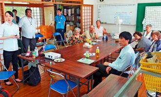 快眠アドバイザーの小那覇夏希さん(左)から話を聞く参加者たち=8月25日、八重瀬町・外間高層住宅集会所