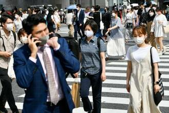 東京・渋谷のスクランブル交差点をマスク姿で歩く人たち=11日午後