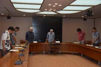 委員会の冒頭で、翁長雄志前知事に黙とうをささげる県民葬実行委員会のメンバー=27日午前、県庁