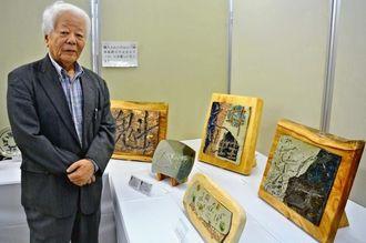 陶芸と書芸の共同制作の作品を紹介する書家の泉泰光さん=24日午後、浦添市民体育館