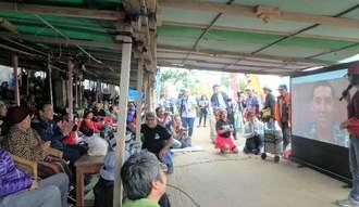 テレビ電話でロブ・カジワラさん(右手スクリーン内)と交流する市民=5日、名護市辺野古・キャンプ・シュワブゲート前