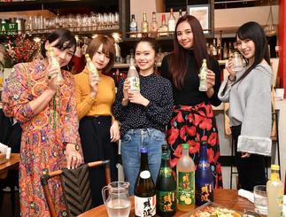 泡盛を手に撮影を行うインフルエンサーの女性参加者=18日、東京・大塚の飲食店「シスイドゥー」