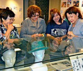 翁長雄志前知事が残した言葉や写真に見入る妻の幹子さん(左から2人目)=日、タイムスギャラリー