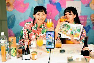 動画配信サイトで生中継し、県産のマンゴージュースを中国の視聴者に売り込むリンピンさん(左)=14日、北谷町・レクー沖縄北谷スパ&リゾート