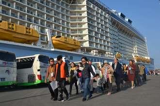 寄港した大型クルーズ船「クァンタム・オブ・ザ・シーズ」から降り、観光地へ向かう乗船者=24日午前、中城湾港