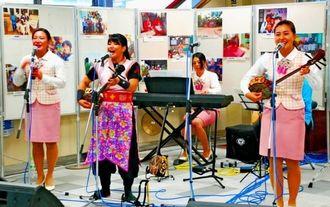 チャリティーイベントで沖縄民謡を披露するバスガイドたち=13日、那覇市・おもろまち駅