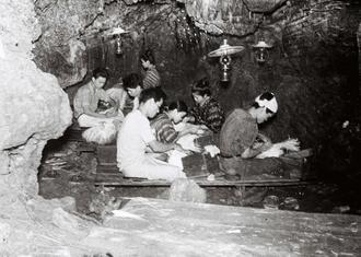 洞窟内でパナマ帽(アダン葉帽)を編む男女。最盛期には黒糖に次ぐ県外への輸出品目だった。昼間に畑仕事をする農家ではなく、時間的に余裕のある若い女性らが内職として作業をすることが多かった。男女掛け合いの沖縄民謡「帽子くまー」では、作業を通して恋の駆け引きが歌われる。原料はパナマ草からアダンの葉に変わったが、乱獲で葉が減少し、細く裂いた紙を寄り合わせてひも状にした「紙縒(こより)」が使われるなど変化した。(写真は朝日新聞社提供)