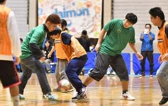 フットサルで熱戦を繰り広げる参加者=7日、沖縄市・県総合運動公園体育館