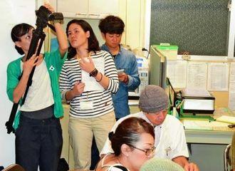 公設市場関係者らが議論する様子を撮影する(左から)宮里侑希さん、新田いずみさん、中須賀章人さん=那覇市・第一牧志公設市場