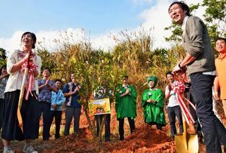 「初めての共同作業」としてシークヮーサーの木を植樹する品地一樹さん(前列右)と智恵さん(同左)夫婦=2日、名護市・勝山シークヮーサー