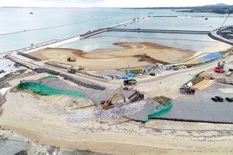 新たな護岸を造るため、石材を敷き詰めるパワーショベル(手前中央)。後方は土砂投入が続く海域=28日午後2時13分、名護市辺野古(小型無人機で撮影)