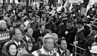 オスプレイの沖縄配備反対などを訴える沖縄のデモ行進に、日の丸を手にした沿道の一団から「売国奴」「日本から出ていけ」などの声が浴びせられた=2013年1月27日、東京・銀座