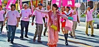 国際通りを練り歩き、乳がんの早期検診を呼び掛ける「ピンクリボン沖縄」実行委のメンバーら=18日、国際通り