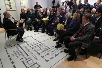 18日、ロシア・サンクトペテルブルクで第2次大戦の参加者らと会談するプーチン大統領(左)(タス=共同)