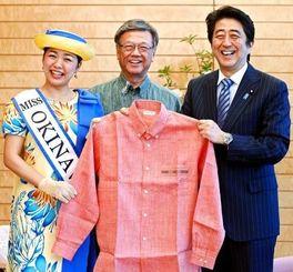 翁長雄志知事(中央)とミス沖縄の町田彩美さんからかりゆしウエアを贈られ笑顔の安倍首相=25日午後、首相官邸