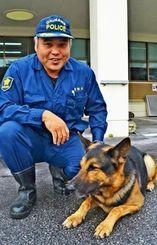 警察犬「アポロ」のことを「甘えん坊ですが、厳しい訓練でもへこたれない強さがある」と話す安次嶺秀樹巡査部長=14日、宜野湾署