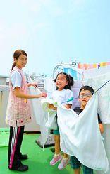 屋上に干された洗濯物の間ではしゃぐ園児たち=16日午後、那覇市牧志・愛育保育園(松田興平撮影)