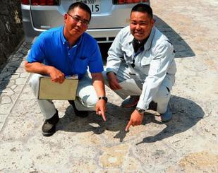 与那原町職員が指さす町章が描かれた石畳。他にも多くのマークが隠されている=与那原町・親川通り